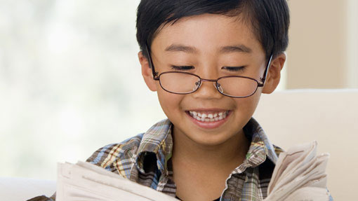 Little boy with reading glasses and smiling while reading a paper